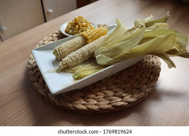 Ears of corn in the process of eating with corn husks, whiskers, and kernels. Eating corn kernel by kernel.