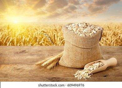 Ears of oats and oatmeal in bag on table with ripe cereal field on the background. Uncooked porridge