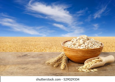 Ears of oats and oatmeal in bowl on table with field on the background. Uncooked porridge
