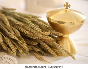 ears of wheat and golden chalice on an altar in a church