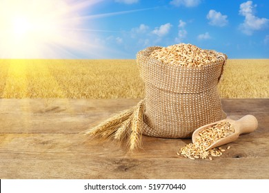 Ears of wheat and grains in bag on wooden table with field on background