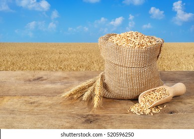 Ears of wheat and grains in bag on table with field on background