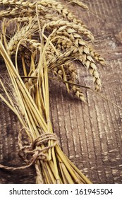 Ears of wheat on old wooden background. Retro style. Selective focus.