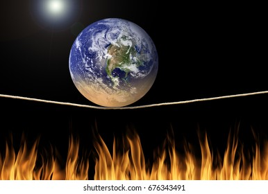 Earth balancing on tightrope over fire flames with the sun in background representing environmental problems, disaster, climate change and death. Some elements provided by Nasa.