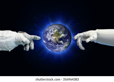 Earth in between astronaut and robotic hand. Elements of this image furnished by NASA.