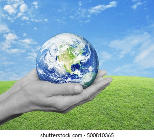 Earth in black and white hands over green grass with blue sky and clouds, Environment concept, Elements of this image furnished by NASA