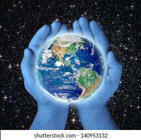 earth in blue hands on black background .Elements of this image furnished by NASA