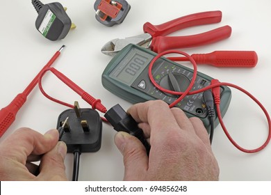 Earth continuity testing – An electrician testing a mains cable earth with a multimeter
