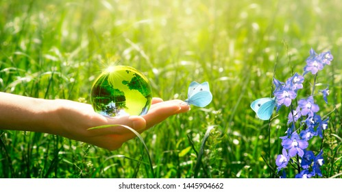 Earth crystal glass globe and butterfly with blue wings in human hand on grass and bluebell flowers background. Saving environment and clean green planet concept. Card for World Earth Day concept.