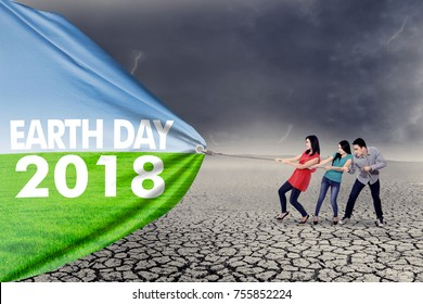 Earth Day 2018. Three people pulling a banner with text of Earth Day 2018