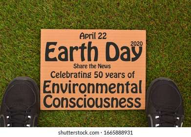 Earth Day April 22 Celebrating 50 years of Environmental Consciousness cardboard sign on green turf grass between sneakers