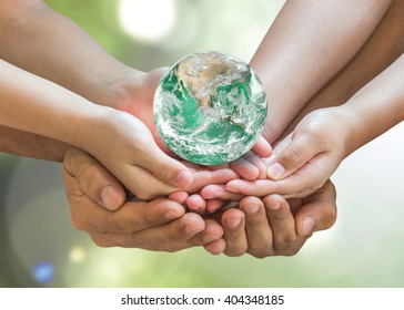 Earth day and charity concept with green planet  in family volunteer hands. Elements of this image furnished by NASA.