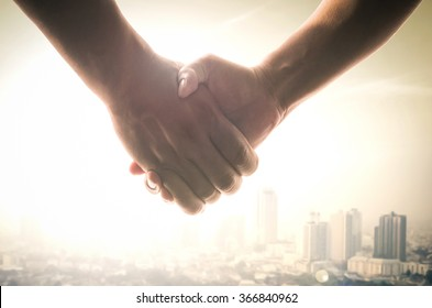 Earth day concept: Advocacy and client shaking hands after good deal on blurred big city background
