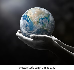 Earth day concept: Planet in black and white human hands. Elements of this image furnished by NASA
