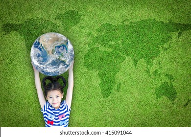 Earth day, ecological friendly and corporate social responsibility, CSR with people, go green and sustainable environment concept with kid raising world on lawn: Element of the image furnished by NASA