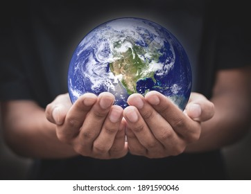 Earth day. Human hands holding global over blurred black background. earth in hands. save the earth. environment concept.