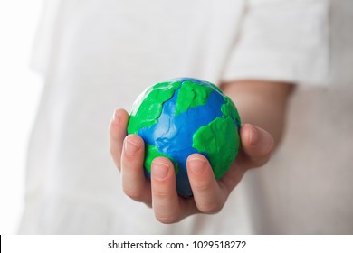 earth day, nature, conservation, environment and ecology concept - close up of  hand holding planet on white background