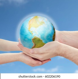 earth day, nature, conservation, environment and ecology concept - close up of child and father hands holding planet over blue sky background