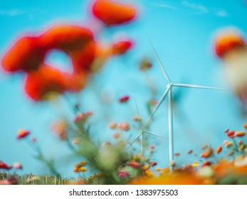 earth day and renewable energy concept with white wind turbine and beauty sky in summer background and soft focus tropical flower on foreground