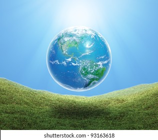 Earth floating over a grass field