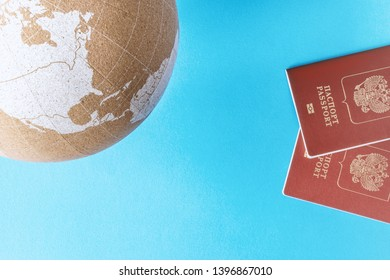 Earth globe cork model and two passports on blue background view from top. Traveling overseas concept. Copy space, template.