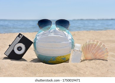 Earth globe dressed in a medical mask. Summer accessories. Turism durung coronavirus. Summer vacation and healthy lifestyle concept. World quarantine. Coronavirus epidemic in the whole world. Top view