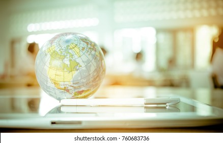 Earth globe model ball map with class room background on tablet in classroom. Concept for global international educaiton or communications, politics environmental for learning world wide. vintage tone