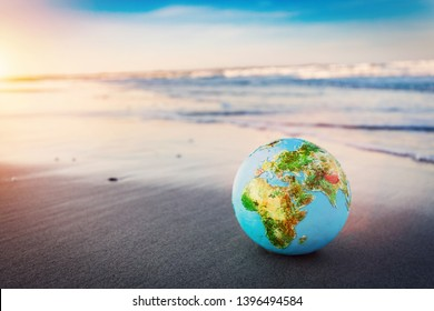 Earth globe on the beach. Concept of environment protection, save the planet, ecology.