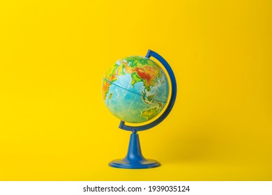 Earth globe on clean yellow background. Education, school, study and knowledge background concept.