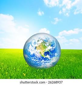 Earth globe on green grass conceptual