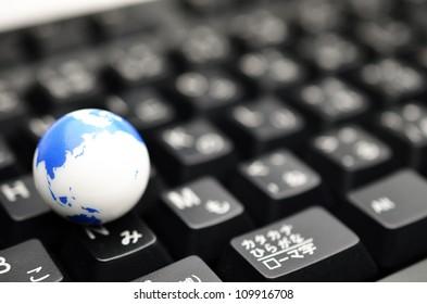 Earth globe over keyboards