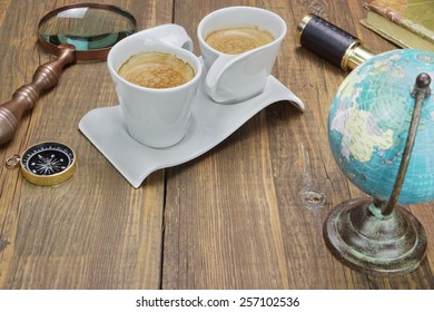 Earth Globe, Vintage Spyglass, Magnifying Glass, Compass, Two Notebooks, Smoking Pipe, and Two Espresso Coffee Cups On The Grunge Wooden Table