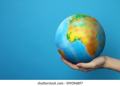 The Earth in hand on blue background. Earth Day.