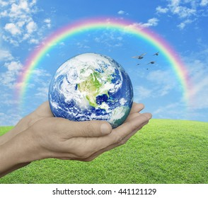 Earth in hands over green grass with blue sky, cloud, rainbow and bird, Environment concept, Elements of this image furnished by NASA