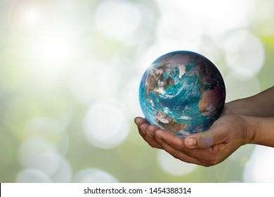 Earth was holding in human hands on blurred. World environment day and green earth. Energy saving environment nature conservation concept with space for text. Elements of this image furnished by NASA