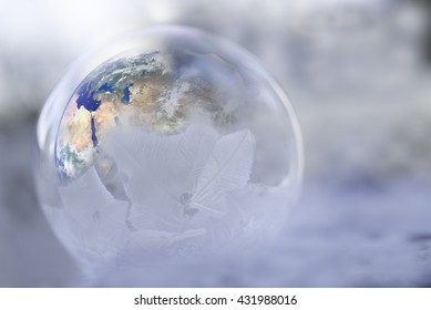 The earth inside a half frozen globe showing impact of global warming in the north and cooling on the south.