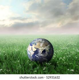 Earth lying on a green lawn