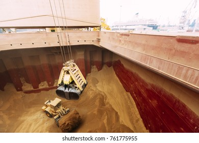 An earth mover arranging the gluten inside the pit of a grain freighter ship, for easier access for the machinery that is emptying the pit.