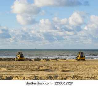 earth movers working in their equipment machines at the beach for maintenance moving the sand