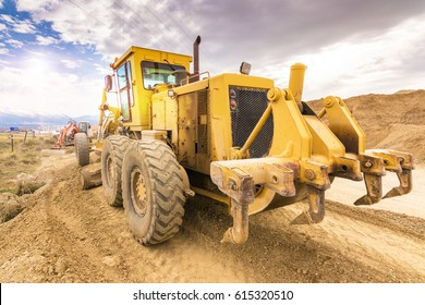 Earth moving by a bulldozer in the construction of a road in Spain. Hydraulic hammer for backhoe