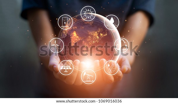 Earth at night was holding in human hands with energy resources icon. Earth day. Energy saving concept