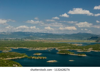 Earth patches and clouds/Landscape image with a lake having small islands and the cloud patches in the sky with mountains in the background.