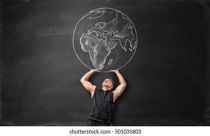 The Earth pictured on a black background and a sporty man acting like he is holding it up above himself. Power of sport. Building muscles with fitness. Running the world.