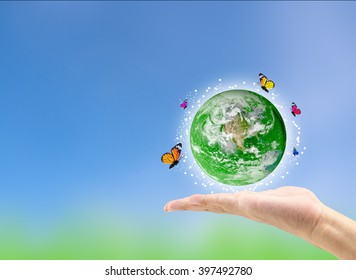 Earth planet with butterfly in hand against green blurred background. Earth day. Spring holiday concept. Elements of this image furnished by NASA