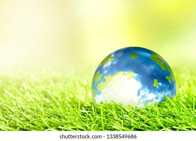 Earth planet on the green grass with green background. Earth hour concept