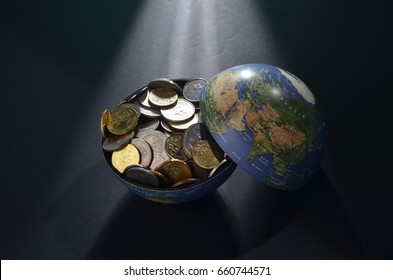 Earth replica filled/insert with money. Studio shoot with creative lighting