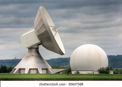An earth station satellite installation with ancillary building - the type used for broadcasting. Poor weather.