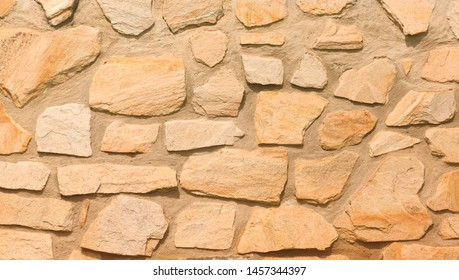 Earth tone flagstone wall background texture.