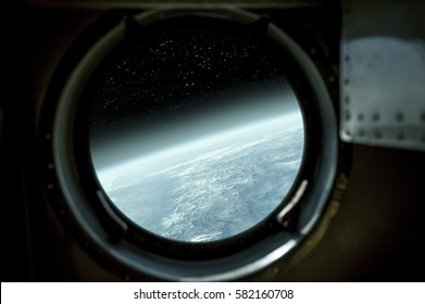 """Earth view through the window of a space ship. """"Elements of this image furnished by NASA"""""""