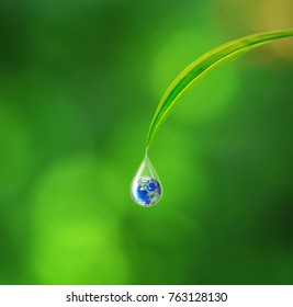 Earth in water drop reflection under green leaf, Earth and water concept, Elements of this image furnished by NASA